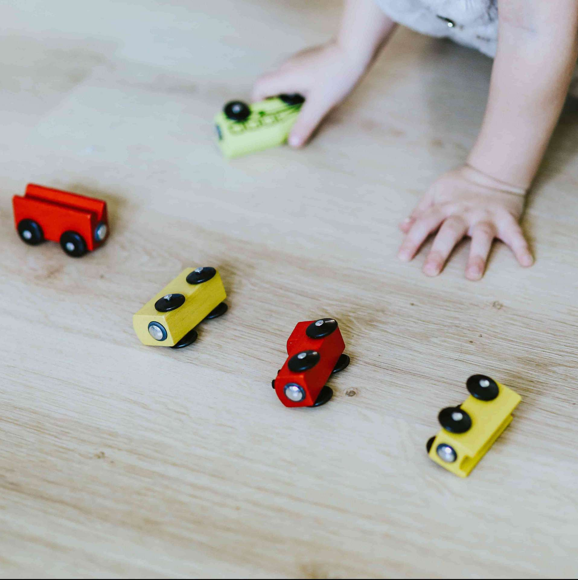 kid playing with wooden cars on hardwood floor
